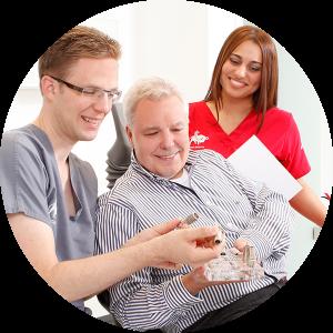 Dr. Jan Wagner erläutert einem Patienten Zahnimplantate